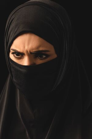 Portrait of aggressive muslim woman in hijab isolated on black Imagens