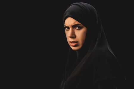 Side view of offended muslim woman looking at camera isolated on black