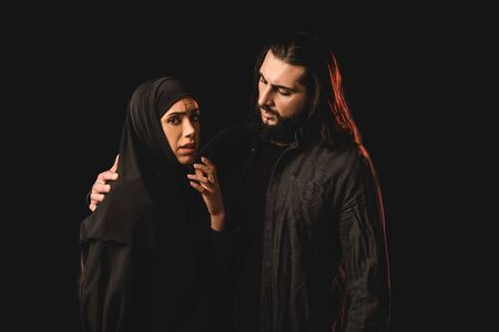 Muslim man embracing worried wife isolated on black Imagens