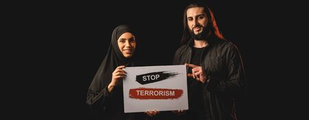 Panoramic orientation of smiling muslim couple holding card with stop terrorism lettering isolated on black