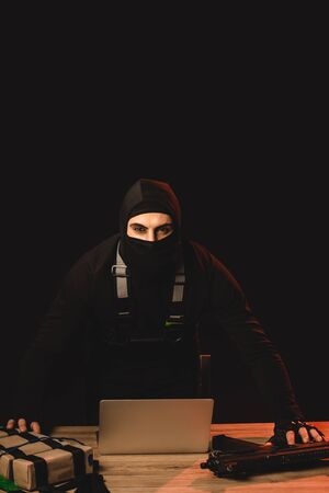 Muslim hacker in balaclava holding explosive belt and machine gun near laptop on table isolated on black Imagens