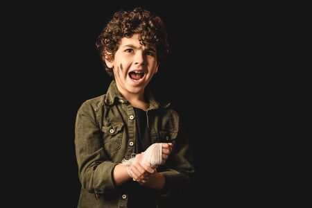 Screaming muslim child with dirty face touching hand in bandage isolated on black