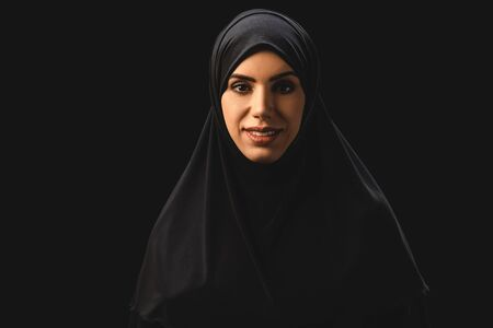 Beautiful muslim woman smiling at camera isolated on black