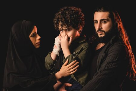 Muslim parents hugging son with injured hand isolated on black