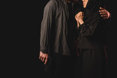 Cropped view of man holding gun and embracing wife in hijab isolated on black Imagens