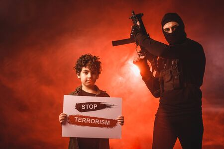 Terrorist in balaclava holding machine gun near muslim boy with stop terrorism lettering on card on black background with red smoke