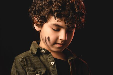 Curly muslim kid with messy face isolated on black