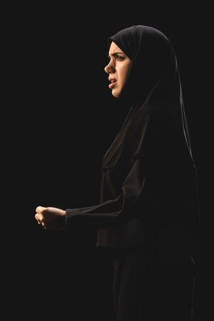 Side view of angry muslim woman looking away isolated on black