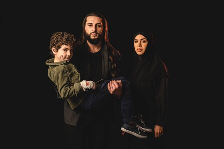 Muslim man holding child with injured hand near wife in hijab isolated on black