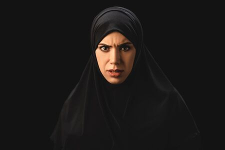 Angry muslim woman in hijab looking at camera isolated on black