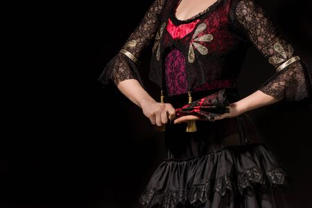 cropped view of young flamenco dancer holding fan isolated on black