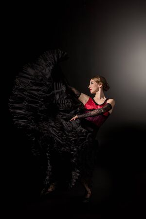 happy and young flamenco dancer in dress dancing on black
