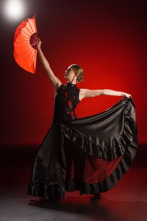 elegant flamenco dancer in dress holding fan while dancing on red