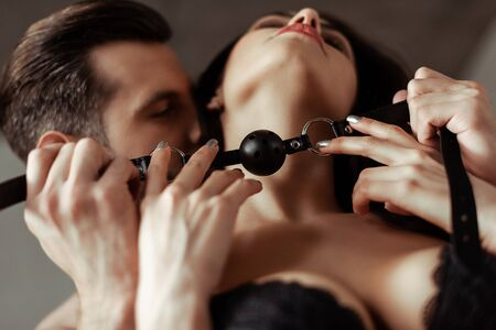 selective focus of sexy beautiful young couple with black gag