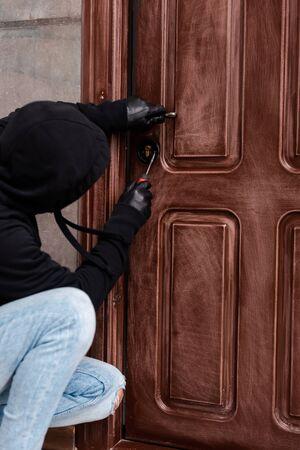 Side view of housebreaker opening door lock with screwdriver Stockfoto