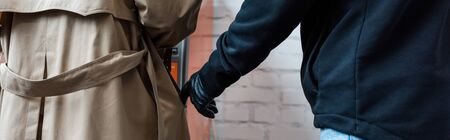 Panoramic shot of robber in leather glove putting hand in pocket of female coat Stockfoto