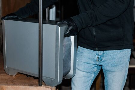 Cropped view of robber taking wireless speaker from cupboard during stealing Stockfoto