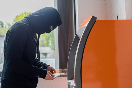 Side view of robber in mask holding credit cards near automated teller machine Stockfoto