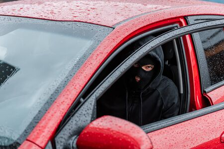 Selective focus of robber in balaclava looking at camera while sitting in car with open door