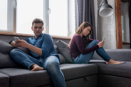 man and woman sitting on sofa and using smartphones