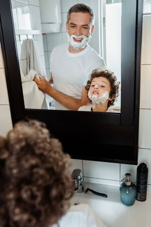 selective focus of curly boy with shaving foam on face looking at mirror near father