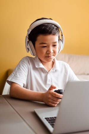 KYIV, UKRAINE - APRIL 22, 2020: asian boy playing video game with joystick and laptop on self isolation