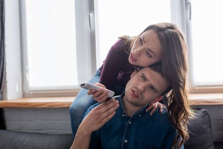 displeased man near woman holding remote controller from air conditioner while feeling hot