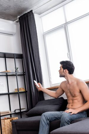 handsome shirtless man with remote controller adjusting temperature of air conditioner at home 스톡 콘텐츠