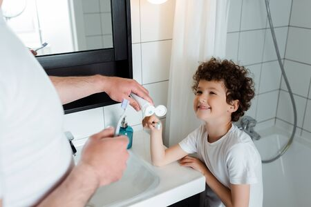 selective focus of father holding toothpaste near toothbrush of cheerful and curly son