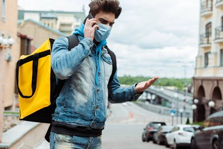 Courier in medical mask pointing with hand and talking on smartphone on city street