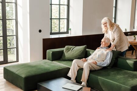 Feliz marido y mujer senior haciendo masajes y relajándose en casa en cuarentena