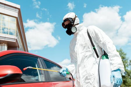 workman in uniform and respirator cleaning car with disinfectant in spray bag during covid-19 pandemic
