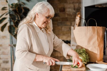 smiling elderly woman cutting vegetables on board for salad on kitchen