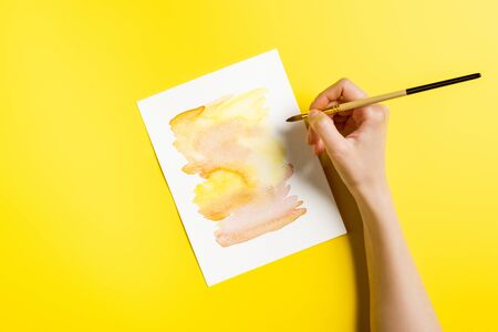 cropped view of artist holding paintbrush near painting on yellow Stock fotó