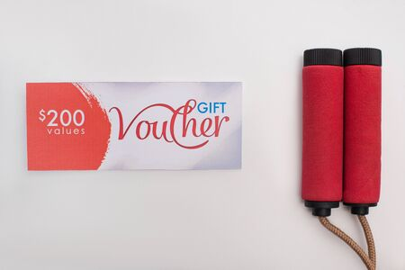 Top view of gift voucher with 200 dollars sign near jump rope on white background