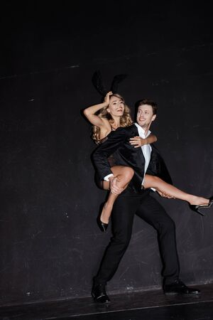 Attractive woman in rabbit ears smiling while piggybacking on boyfriend in suit on black background