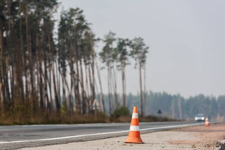 roadwork cones near highway with car moving with lighting headlamps in ukraine Reklamní fotografie
