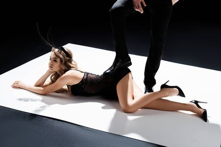 Man putting foot on hip of sexy woman in bunny ears lying on white surface on black background