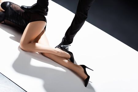 Cropped view of man putting foot on sexy woman lying on white surface on black background Stok Fotoğraf