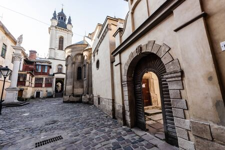 street leading to carmelite church and monastery wall with arch in lviv, ukraine