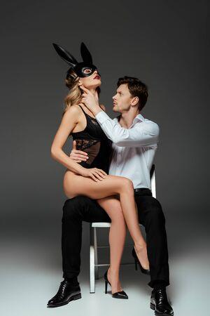 Hombre guapo tocando el cuello de la novia en la máscara de conejo mientras está sentado en una silla sobre fondo gris