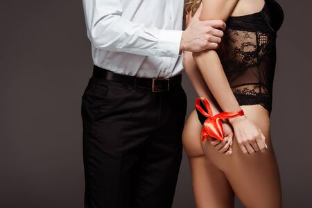 Cropped view of man touching sexy woman with tying hands isolated on grey