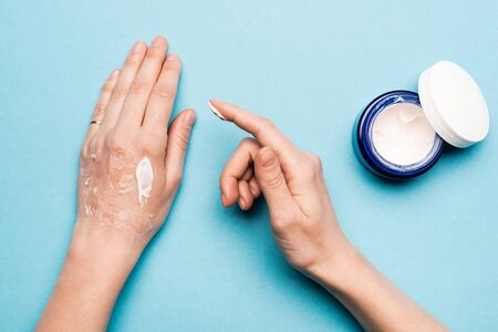 cropped view of woman applying hand cream on dehydrated, exfoliated skin on blue Foto de archivo