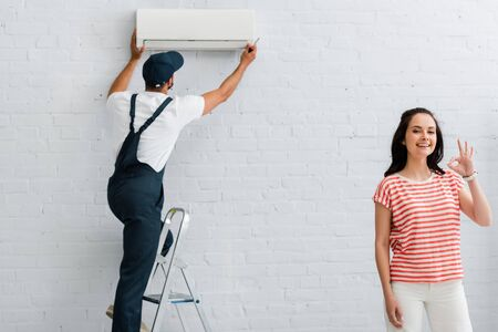 Smiling woman showing ok gesture while repairman fixing air conditioner