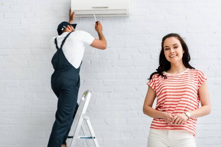 Selective focus of smiling woman looking at camera while workman fixing air conditioner