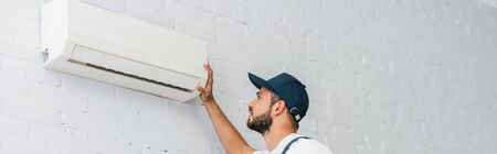Panoramic crop of workman looking at air conditioner on wall Stock fotó