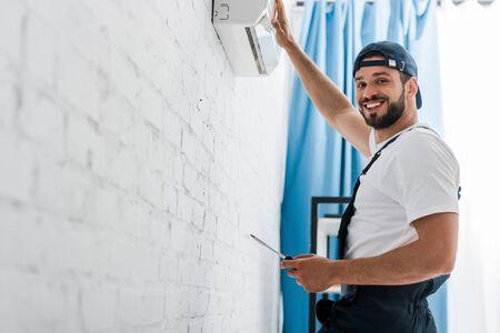 Smiling workman looking at camera while repairing air conditioner