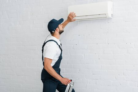 Side view of workman in uniform holding screwdriver while fixing air conditioner on wall Stock fotó
