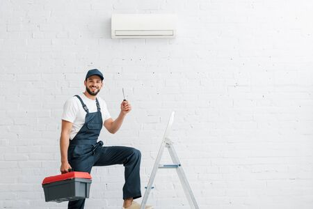 Smiling workman in uniform holding screwdriver near ladder and air conditioner on wall Stock fotó