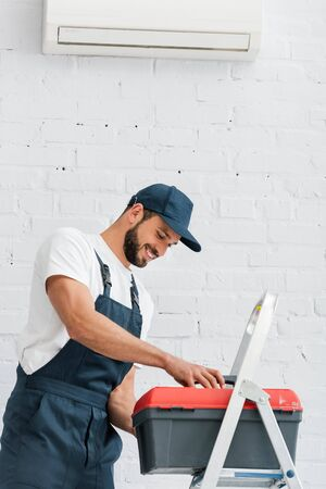 Smiling workman in uniform holding toolbox near ladder and air conditioner on white wall